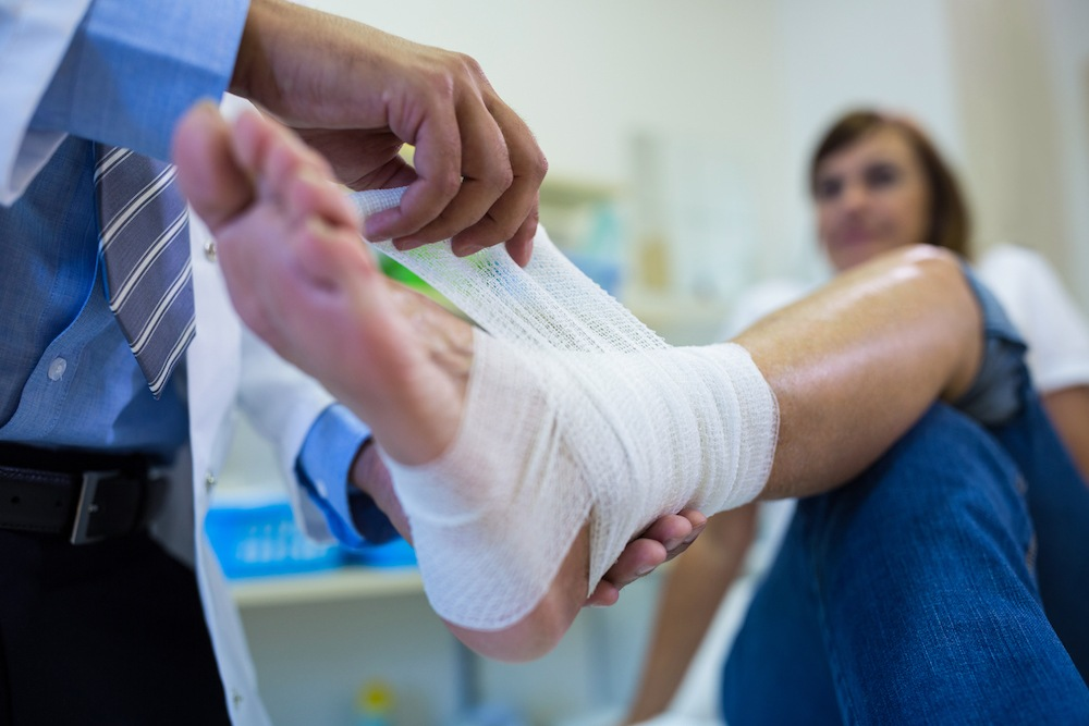 Doctor bandaging foot of patient